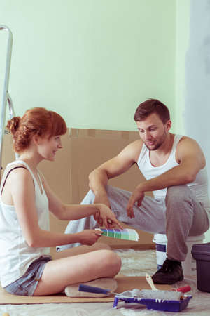 redecoration: Shot of a young couple sitting in a room they redecorate and choosing a colour from a colour swatch