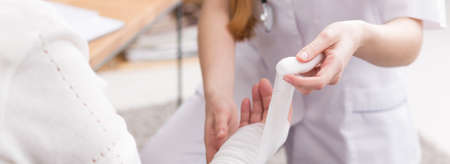 Close-up of young nurse in a duster dressing older careless woman's wound on a hand
