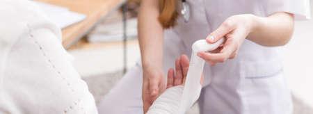 Közelkép, fiatal nővér egy poroló öltözködés idősebb gondatlan nő sebét a kezét