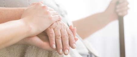 Panorama-Bild von einer Frau, die ihre Großmutter die Hand unterstützend halten