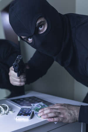 gun room: Shot of a masked robber pointing a gun at the camera