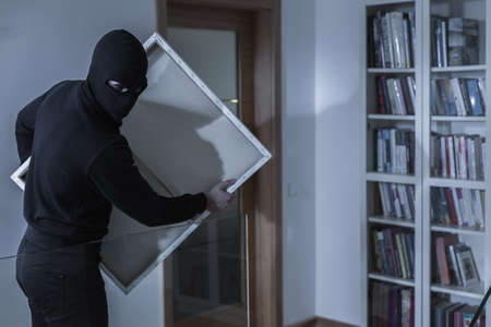 breakin: Shot of a masked thief holding a painting Stock Photo