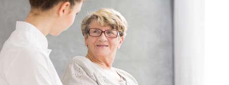 persona de la tercera edad: Captura de una mujer mayor sonriente y mirando a su joven cuidador Foto de archivo
