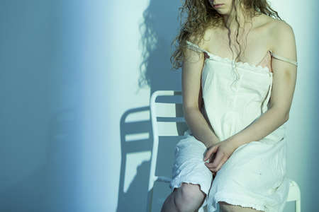 devastated: Young, devastated woman with bruises, sitting on a chair in an empty room Stock Photo