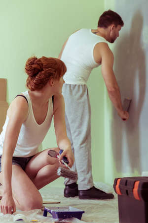 redecorate: Shot of a young woman looking at her boyfriend painting a wall