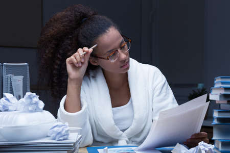revise: Young woman working at night at a desk filled with sheets of paper and books