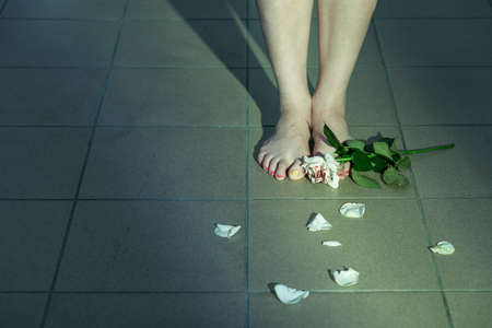 abused women: Close-up of womans feet on a tiled floor, with a rose and rose petals scattered around