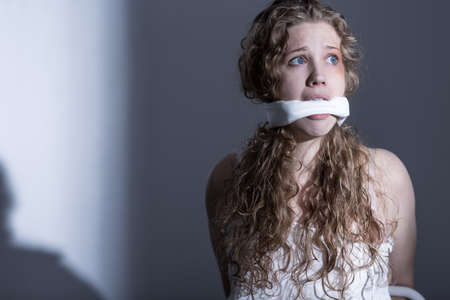 hijacked: Terrified young woman in an empty room, having her mouth gagged Stock Photo