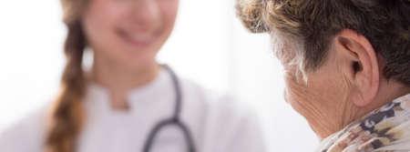 persona de la tercera edad: Primer plano de una mujer enferma de más edad feliz de su joven enfermera de cuidar de ella