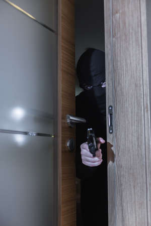 breakin: Shot of a burglar holding a gun and sneaking into a room