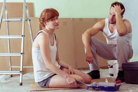 redecoration: Shot of a tired young couple sitting on a floor in a flat they redecorate