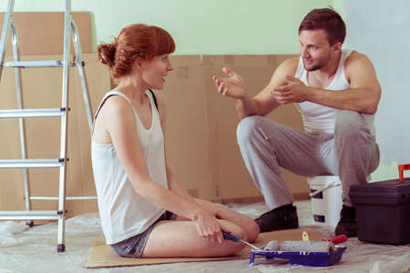 redecorate: Shot of a young couple talking in a room they renovate Stock Photo