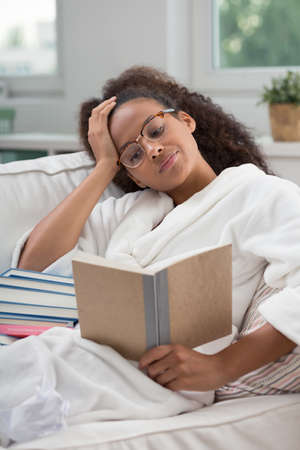 bored woman: Young, bored woman in a dressing gown, reading a book on a white sofa