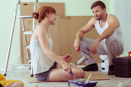 redecorate: Shot of a young couple sitting on a floor in their flat and holding paint rollers Stock Photo