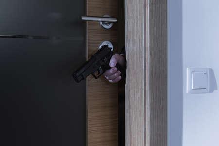 breakin: Shot of a burglars hand holding a gun