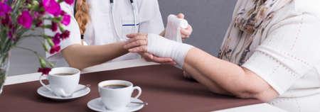 herida: Primer plano de la joven enfermera cuidando de mujer mayor. Cuidador de apósito para heridas de un paciente. Junto a ellos dos tazas de café Foto de archivo
