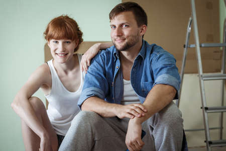 refurbishment: Shot of a young happy couple taking a break from redecorationg their flat