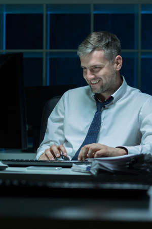 work addicted: Man addicted to his work, sitting at office at night Stock Photo