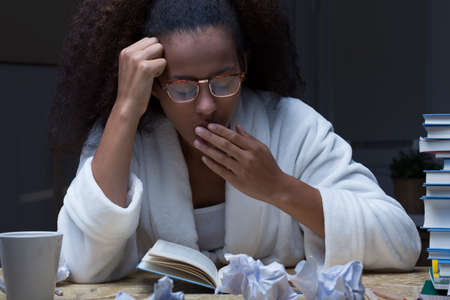 Close-up of a young dark-skinned student learning in the middle of the night, tired and yawning