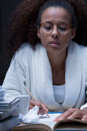 copybook: Portrait of a young woman taking notes in her copybook in the middle of the night