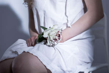 roses and blood: Close-up of a young womans knees on which she is holding a white rose with red stains Stock Photo