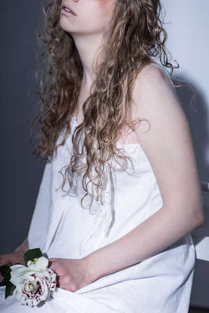 abuso sexual: Foto de una mujer joven, devastado la celebración de una rosa blanca con manchas rojas en sus rodillas como si un símbolo de algo malo que ha sucedido a su