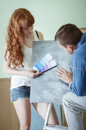 redecoration: Shot of a young couple choosing a colour for the wall