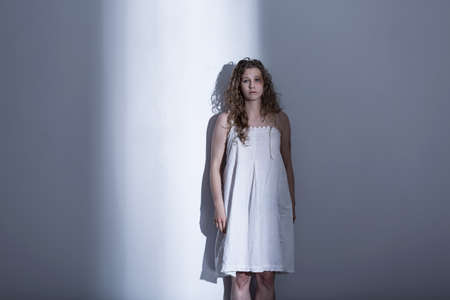rape: Young, brused woman in a nightdress, standing by a white wall in an empty room