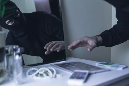 Shot of a robber stealing valuables from a table Stock Photo