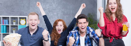 enthusiastic: Cheerful friends watching sport game on tv Stock Photo