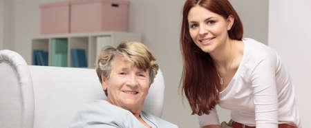 weak: Smiling granddaughter caring about weak grandmother Stock Photo