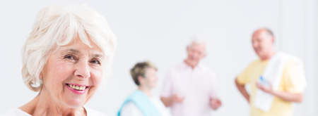 indoor photo: Shot of a happy senior woman and a group of her friends standing in the background