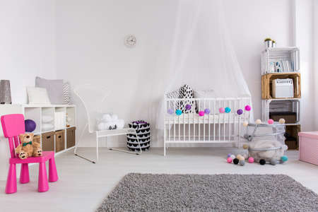 bedroom bed: Modern bedroom of little baby girl. White cradle with canopy, armchair and soft grey carpet on the floor Stock Photo