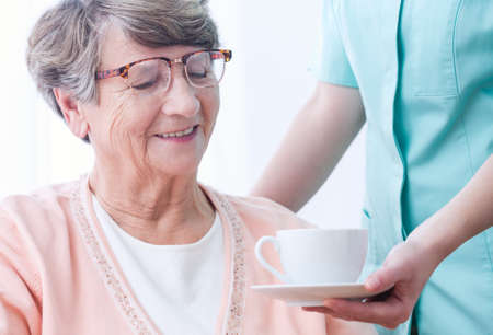 age care: Old lady is given  a cup of tea by her female caregiver Stock Photo