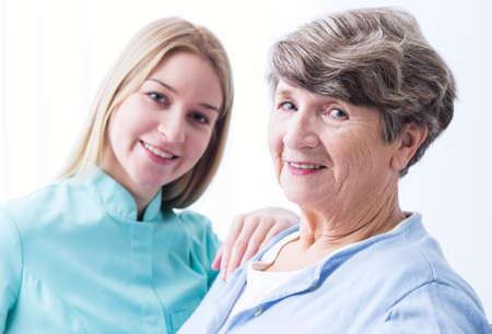 persona deprimida: joven mujer cuidadora y su barrio ancianos están sonriendo