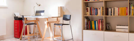 Part of a home office with wooden desk, chairs and bookstand