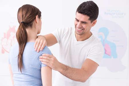 Jonge fysiotherapeut die een schoudermassage geeft aan een jonge vrouw Stockfoto