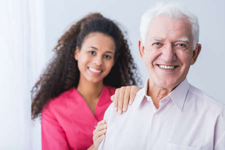 medical attention: Happy carer and smiling senior man standing in light interior. Stock Photo