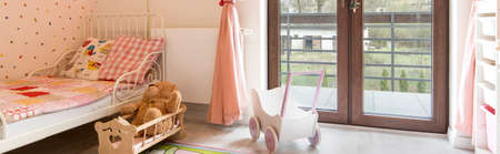 baby toys: Child room for a girl in pastel shades and glass doors to the balcony Stock Photo