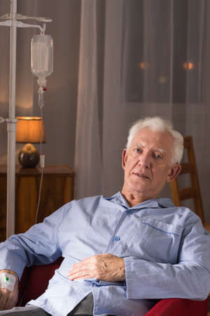 incurable: Senior man with drip sitting on chair in home.