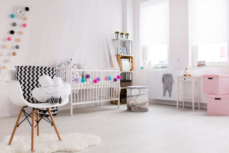Spaziosa camera da letto bianco e rosa con pavimento in legno per il bambino piccolo. culla bianca con decorazioni e tettoia dal muro Archivio Fotografico