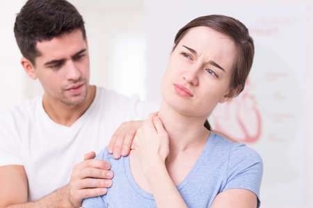 massaged: Photo of a young woman having her painful shoulder massaged Stock Photo