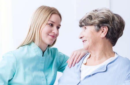solicitude: Young female senior care assistant is looking at elderly woman