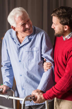 senility: Man assisting senior man with walking zimmer. Stock Photo