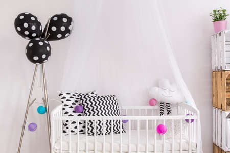 canopy: White cradle with canopy and black and white pillows in little babys bedroom. Next to it stand with balloons