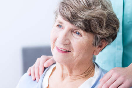 senior depression: Old woman is gently smiling while a caregiver is supporting her from back Stock Photo