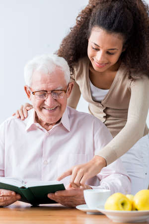 senior lady: Carer standing over senior man which is holding a book.