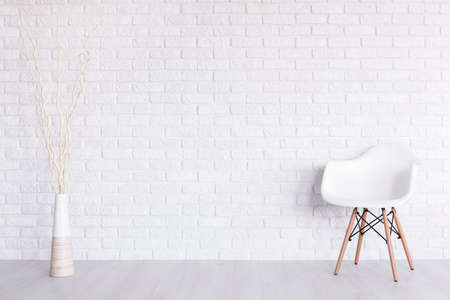 Shot of a white modern room with a chair and a vase Foto de archivo