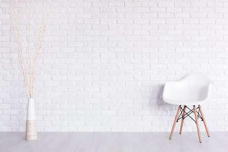 Shot von einem weißen modernen Zimmer mit einem Stuhl und einer Vase