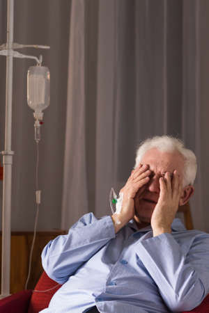 covering face: Senior man with drip, covering face with hands, sitting on chair at home. Stock Photo